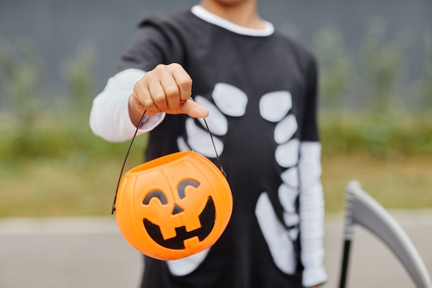 Close up of unrecognizable teenage boy holding halloween pail to camera and wearing costume trick or...