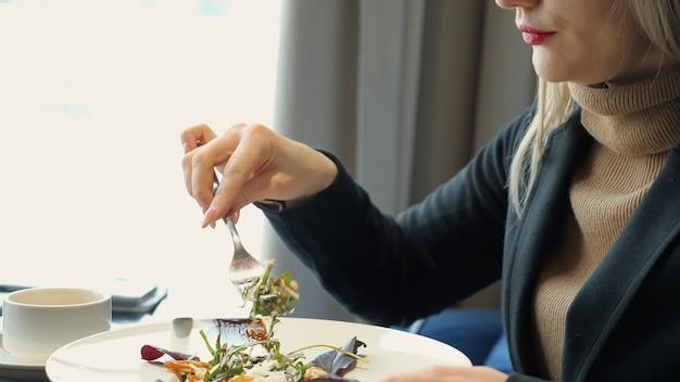 カフェに座ってサラダを食べている認識できない女性を閉じます。