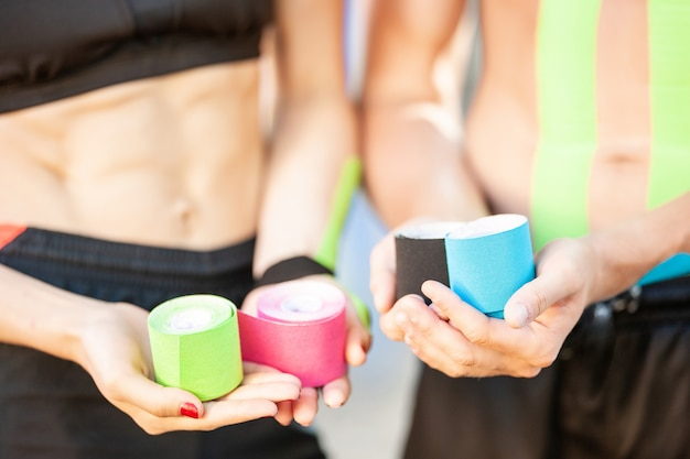Close up of unrecognizable woman and man holding colorful rolls of elastic kinesiology tapes. selective focus of rehabilitation treatment in hands of young sports couple wearing black sportswear.