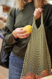 Close-up of unrecognizable woman putting lemon into net bag while buying it at food market