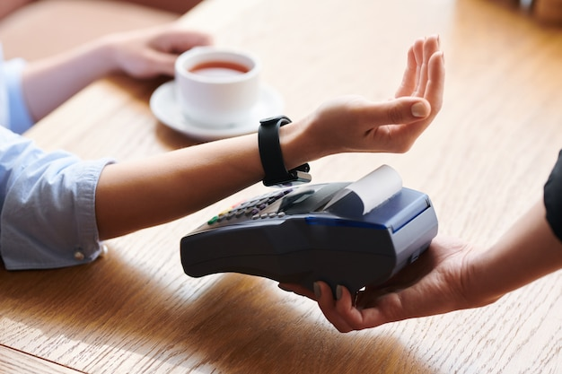 Close-up of unrecognizable woman putting wristwatch to payment terminal while making contactless payment in cafe