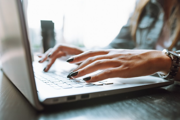 Close up of unrecognizable woman's hands with dark nailpolish using grey laptop computer on desk.