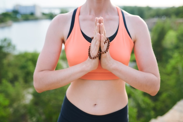 Close-up of unrecognizable woman in sports bra making namaste gesture with mala beads outdoors