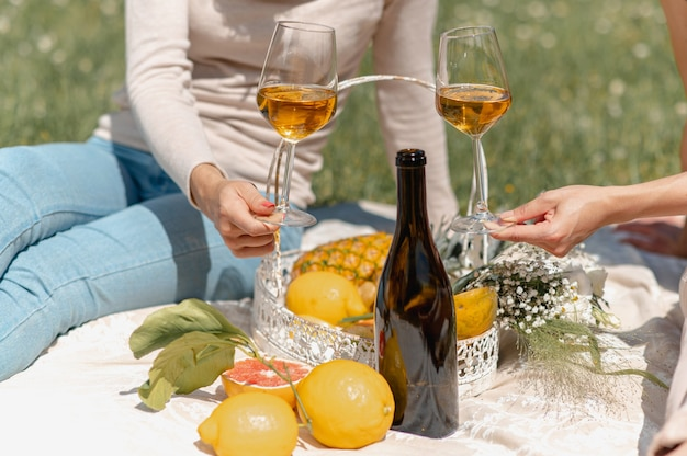 Close-up unrecognizable women holding two glasses with white wine. tropical fruits, flowers and a empty bottle to show the wine flavors. females sitting on blanket having a picnic.