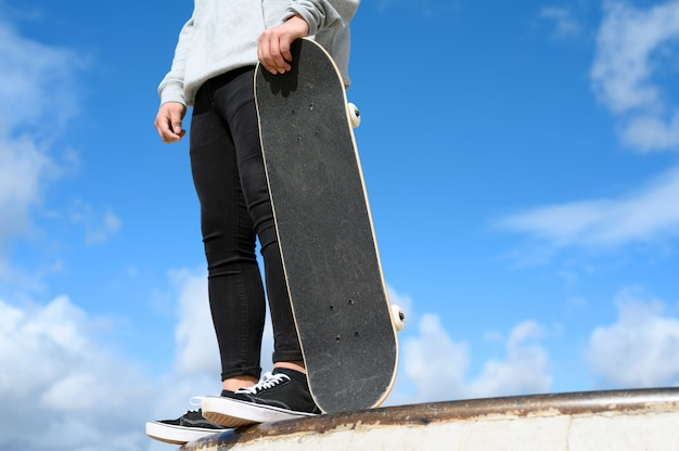 Close up of unrecognizable young man holding skateboard in the park on blue sky background.