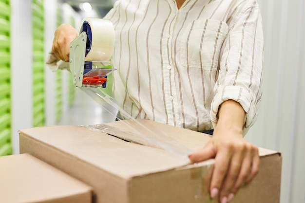Close up of unrecognizable young woman packing boxes with tape gun while standing by self storage unit, copy space