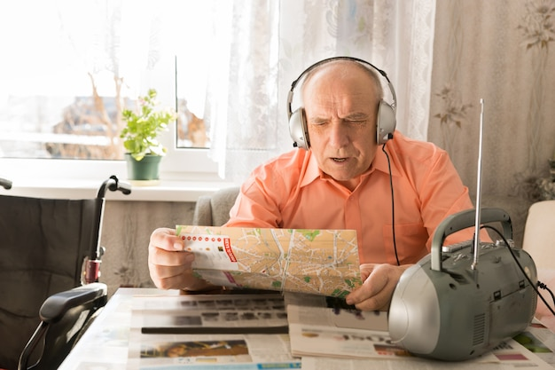 更新された老人の禿げた男を閉じて、居間のテーブルに座って、新聞を読みながらヘッドセットデバイスでラジオから音楽を聴きます。