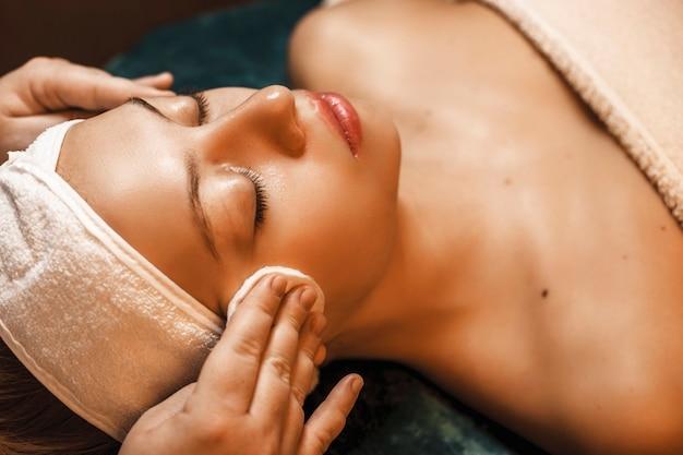 Крупным планом вид очаровательной женщины, проходящей процедуры очистки кожи в спа-салоне.