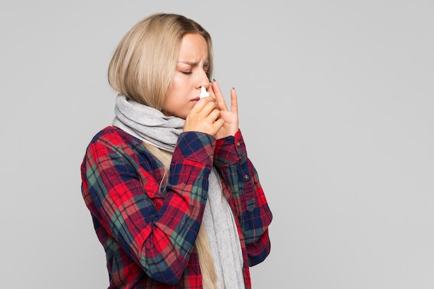 Close up of upset woman in checked shirt wrapped in scarf using nasal spray