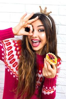 Chiuda sul ritratto urbano della donna hipster brunet divertendosi e impazzendo alla festa in maschera, indossando un maglione accogliente alla moda e una corona del viso, mangiando una torta gustosa dolce ai frutti di bosco, luminosa, positiva, felice.