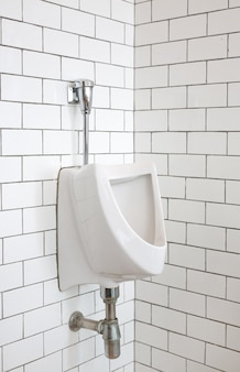 Close-up of urinal for men in public toilet room.
