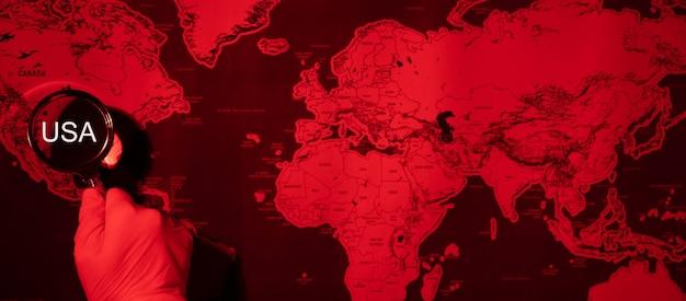 Крупный план сша через увеличительное стекло. абстрактное изображение карта мира коронавируса