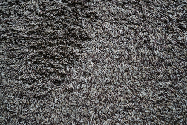 Close up used white - gray - brown doormat for any old vintage design style.