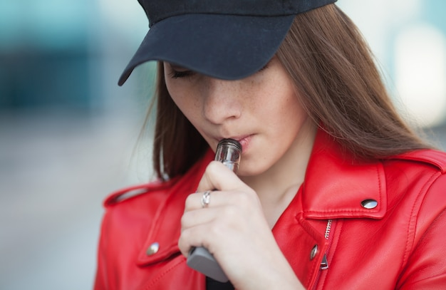 Close up of vaping young girl holding modern e-cig device in lips