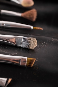 Close-up of various makeup brushes on black background