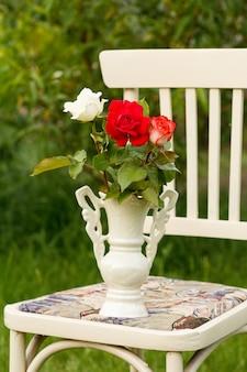 자연 배경이 있는 정원에 있는 흰색 소박한 스타일의 의자에 장미 꽃의 클로즈업 꽃병.