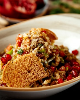 Close up of vegetable salad with walnut pomegranate and bread toast