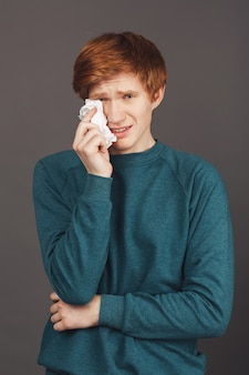 Close up vertical portrait of dramatical ginger good-looking teenager in green sweater holding napkin in hand, wipes up fake tears from face, trying to make friends feeling guilty about abusing him