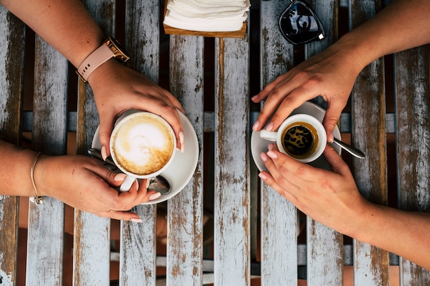 Close up vertical view of couple of females caucasian friends having a coffee and cappuccino break together at the bar