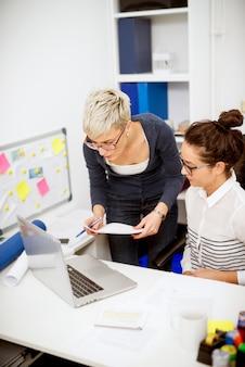Закройте вертикальный вид двух сфокусированных профессиональных продуктивных женщин, работающих вместе друг с другом на ноутбуке в офисе.