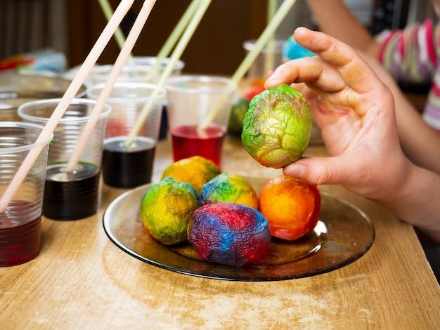 부활절을 준비하는 동안 흰색 삶은 계란에 염료와 그림을 사용하는 아이들의 손에 대한 비디오를 닫습니다