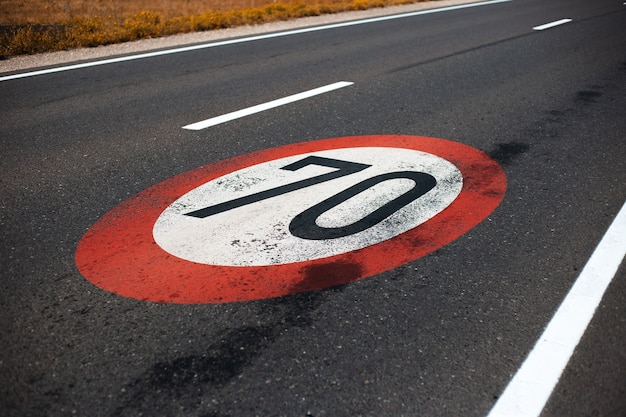 Close-up view of 70 km per hour, speed limit sign painted on dark asphalting road.