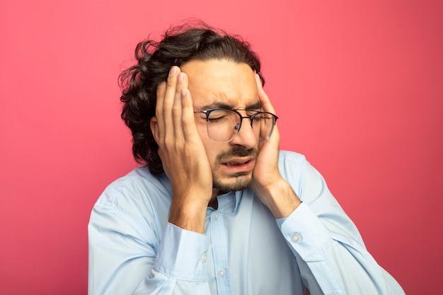 Vista ravvicinata di dolorante giovane uomo caucasico bello con gli occhiali tenendo le mani sulla testa che soffrono di mal di testa con gli occhi chiusi isolati sulla parete cremisi