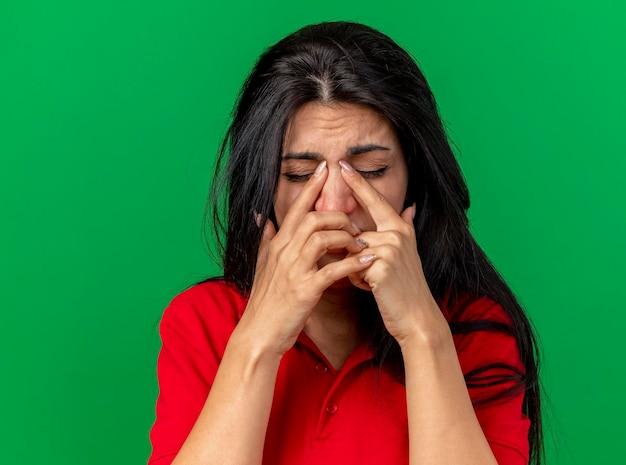 Vista ravvicinata della giovane donna malata dolorante che mette le dita sul naso con gli occhi chiusi isolati sulla parete verde con lo spazio della copia