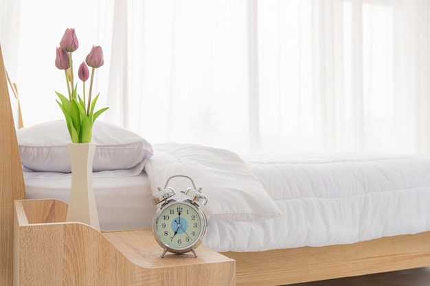 Close up view. alarm clock and tulips flower vase is located on the table at the head on white bed