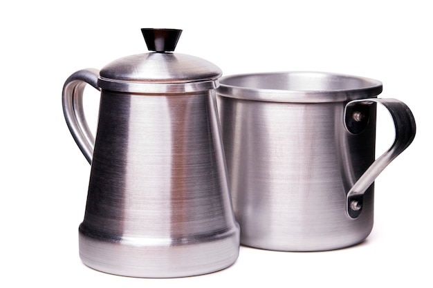 Close up view of an aluminum traditional tea cup and pot isolated on a white background.