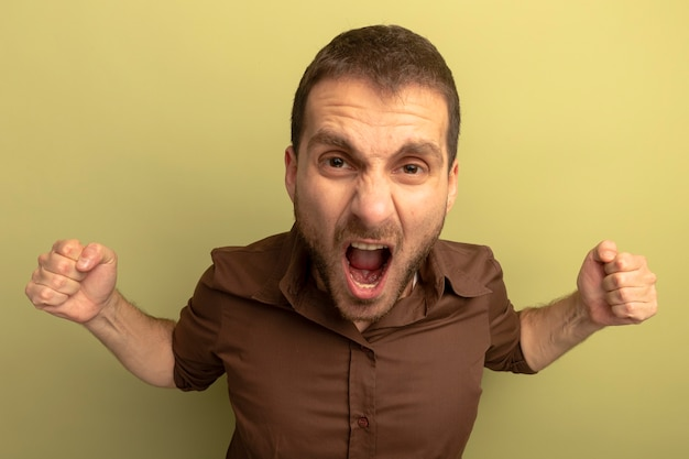Close-up view of angry young man clenching fists screaming isolated on olive green wall