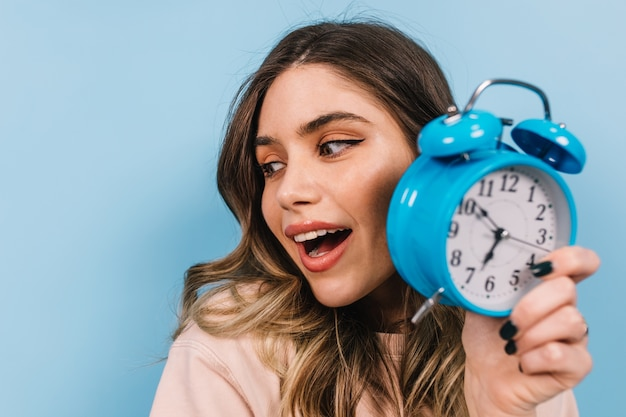 Close up view of appealing woman with clock