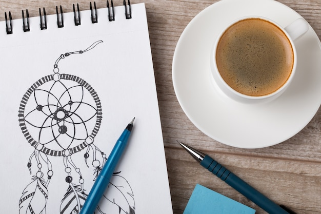 Close-up view of artist's or designer's table. cup of coffee, pencil, fine liner and eraser laying on sketch book with hand-drawn dream catcher
