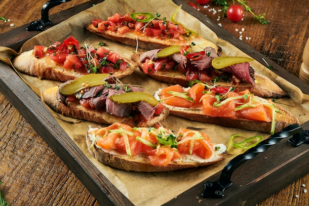 Close up view on assorted delicious bruschetta with salmon, beef and tomatoes on wooden surface. italian appetizer. antipasti.