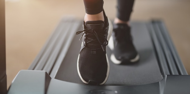 Close-up view of athletic woman running in jogging sneakers on treadmill