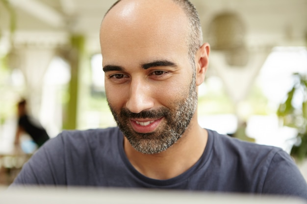 Close up view of attractive adult male with beard sitting at open terrace, typing on laptop, looking at screen with interested smile, using wi-fi to communicate online while away on vacations