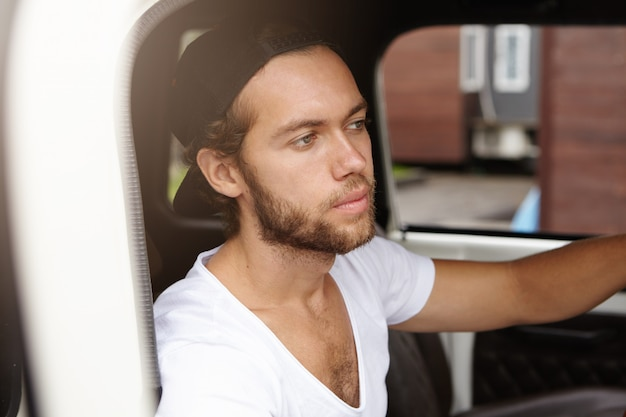 Close up view of attractive young bearded man in snapback sitting inside cabin of his white jeep