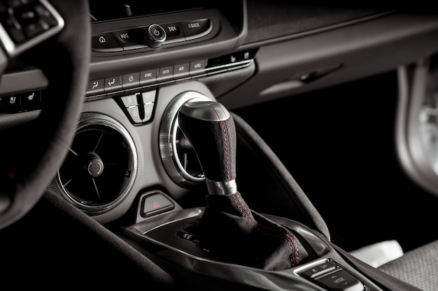 Close up view of the automatic gear lever inside a sports car, black and white