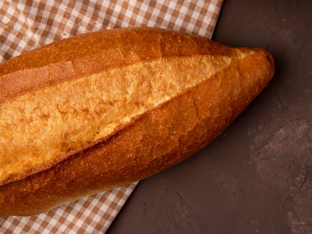Close-up view of baguette on plaid cloth on maroon background with copy space