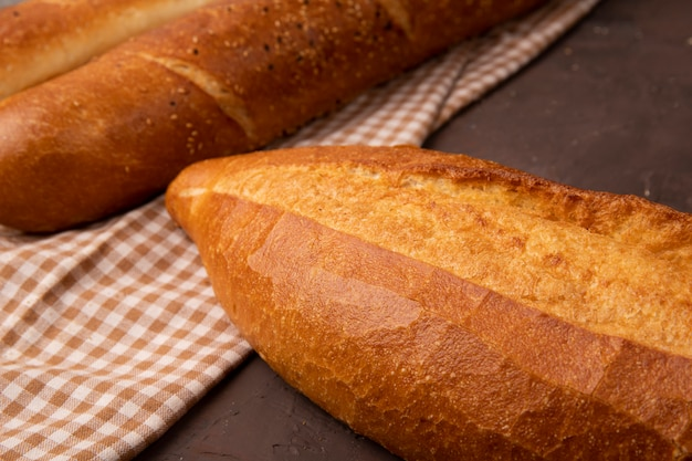 Close-up view of baguettes on cloth on maroon background with copy space