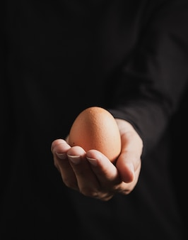 Close-up view baker hand holding egg
