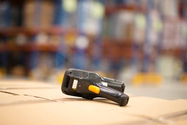 Close up view of bar code scanner placed on cardboard boxes in large distribution warehouse facility