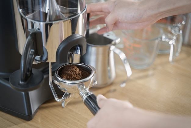 Close up view of barista pulling lever of grinder machine to get grind coffee bean in coffee tamp.