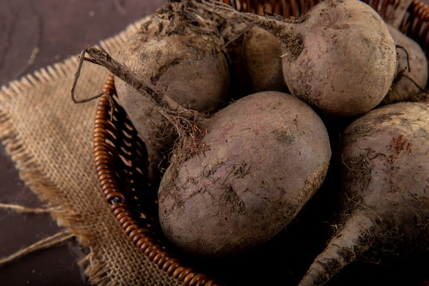 Close-up view of basket of beetroots on sackcloth on maroon background