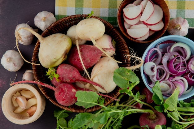 Close-up view of basket and bowls full of vegetables as radish onion and garlic on maroon background