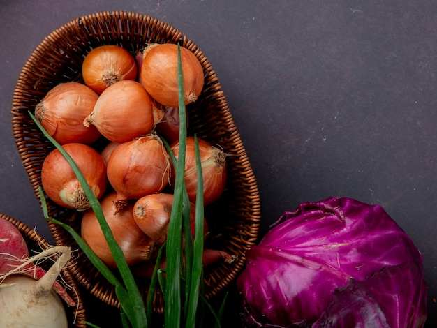 Close-up view of basket full of onion with purple cabbage and scallion on maroon background with copy space