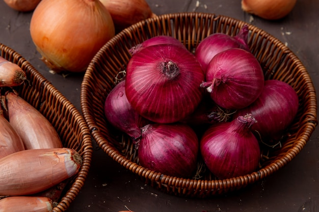 Close-up view of basket of onions on maroon background