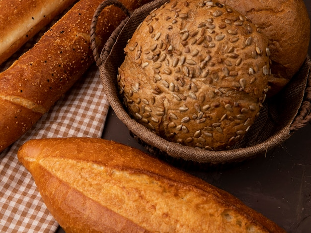 Close-up view of basket of seeded and classic cobs with baguettes on maroon background