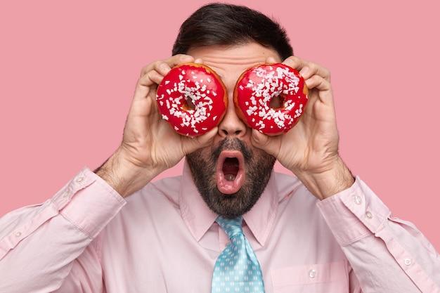 Vista ravvicinata dell'uomo barbuto mantiene ciambelle rosse sugli occhi, mantiene la bocca ampiamente aperta