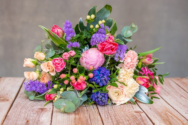 Close up view of a beautiful bouquet of mixed coloful flowers on wooden table.